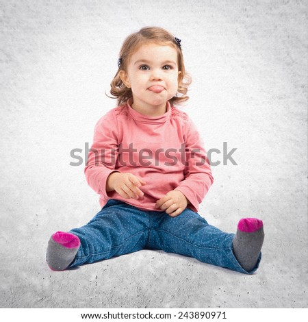 Cute baby girl sticking out tongue over textured background