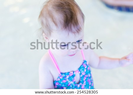 Cute baby girl swimming at indoor swimming pool.
