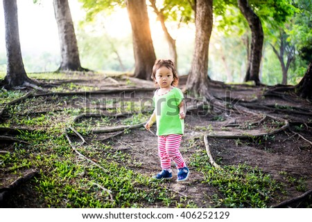 Cute baby girl walking and playing in jungle - stock photo