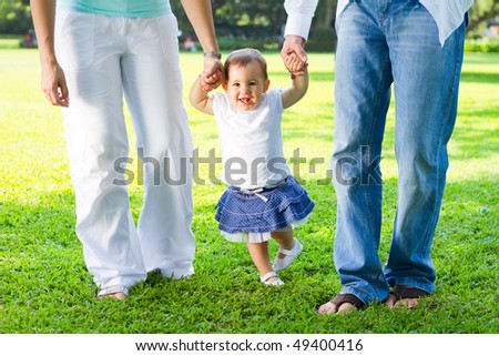 cute baby girl walking in park with parents - stock photo