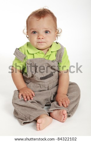 Cute baby girl wearing a green T-shirt and gray pants - stock photo