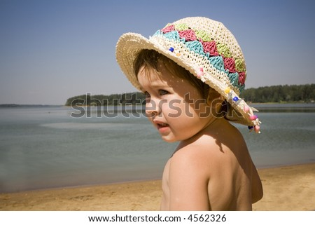 Cute baby girl wearing a straw hat on a lake beach - stock photo