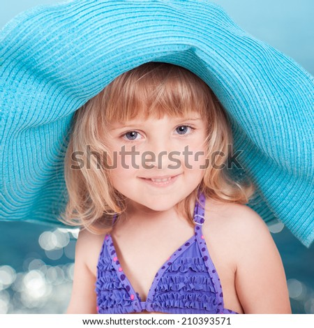 Cute baby girl wearing hat on sea background - stock photo