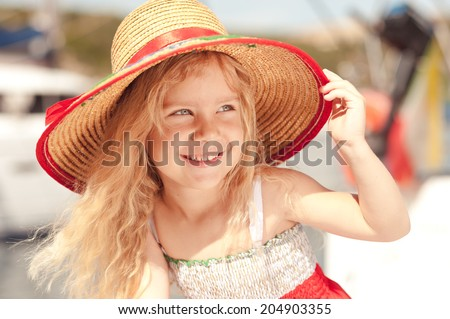 Cute baby girl wearing hat outdoors - stock photo