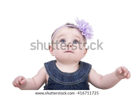 cute baby girl with big blue eyes and long eyelashes. portrait of child on white background, isolated. baby raises his arms up and looking upwards