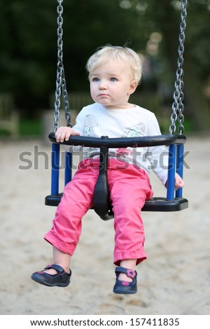 Cute baby girl with blond curly hair having fun on a swing ride at a playground in a sunny summer park
