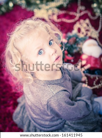 Cute baby girl with curly blond hair and big blue eyes playing with christmas decoration. Selective focus - stock photo