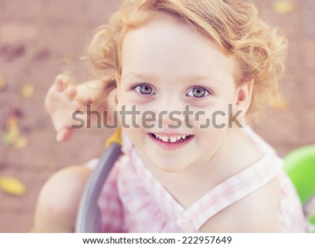 Cute baby girl with curly hair having fun at a park - stock photo