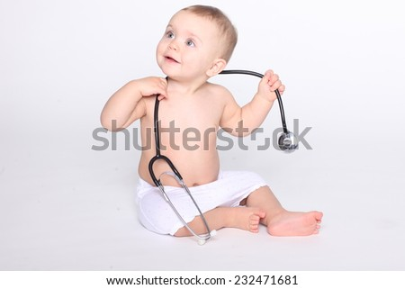 Cute baby girl with stethoscope in hands - stock photo