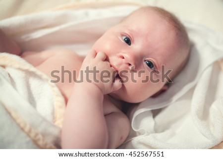Cute baby girl wrapped in a towel sucking fingers. - stock photo