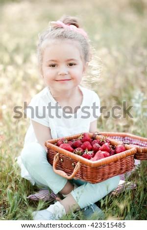 Cute baby girl 3-4 year old having picnic outdoors. Eating fresh strawberry. Looking at camera.  - stock photo