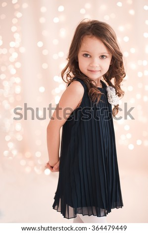 Cute baby girl 5-6 year old wearing stylish dress over lights in room. Looking at camera. Birthday party. Celebration.  - stock photo
