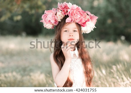 Cute baby girl 3-4 year old with peony wreath outdoors. Looking at camera. Childhood.  - stock photo