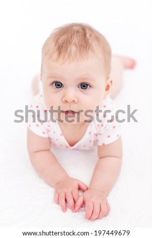 Cute baby girlplaying on a white blanket.