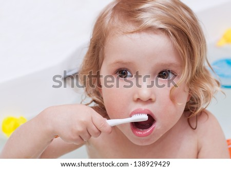 Cute baby have in the bathroom brushing her teeth with a toothbrush