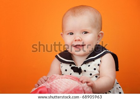 Cute baby in a polka dot dress playing with a toy
