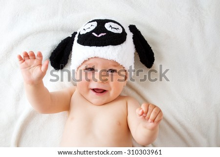 cute baby in a sheep hat lying on soft blanket - stock photo