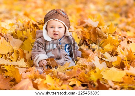 Cute baby in autumn leaves. First autumn - stock photo