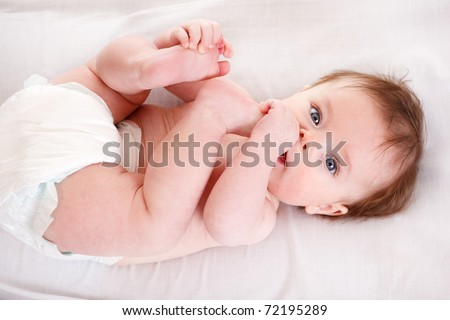 Cute baby in diaper lying with his fingers and toes in mouth - stock photo