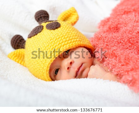cute baby in funny yellow giraffe hat looking in camera, beautiful kid's face closeup - stock photo