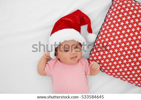 Cute baby in Santa hat on bed, top view