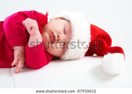 Cute baby in Santa hat sleeping in Christmas night - stock photo