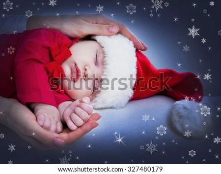 Cute baby in Santa hat sleeping in mother's hands - stock photo
