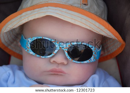 cute baby in sunhat and sunglasses - stock photo
