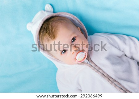 Cute baby in the hood on a blue blanket - stock photo