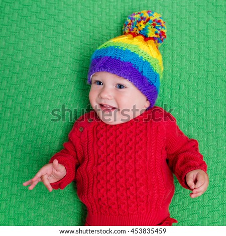 Cute baby in warm wool knitted hat on a green blanket. Autumn and winter clothing for young kids. Colorful knitwear for children. Adorable little boy ready for a walk on a cold fall day. - stock photo