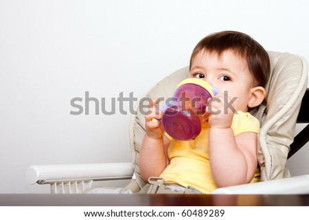 Cute baby infant boy girl sitting in chair drinking from sippy cup. - stock photo