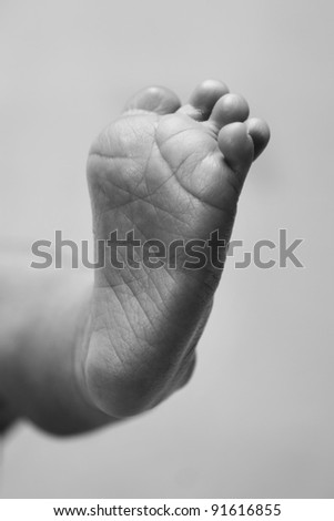 Cute baby infant wrinkled foot sole with toes in black and white, grayscale.