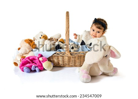 Cute baby inside basket with stuffed animals  - stock photo