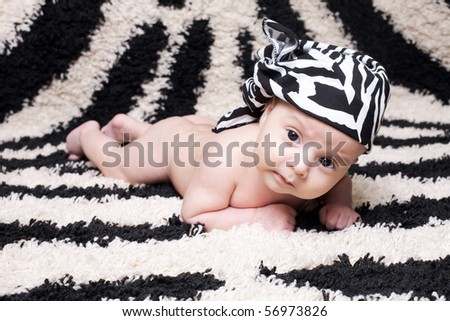 Cute baby is lying on the carpet color zebra