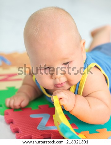 Cute baby is playing toy - stock photo