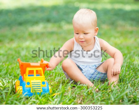 Cute baby is playing toy car - stock photo