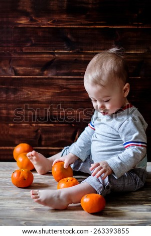 Cute baby is playing with tangerines - stock photo