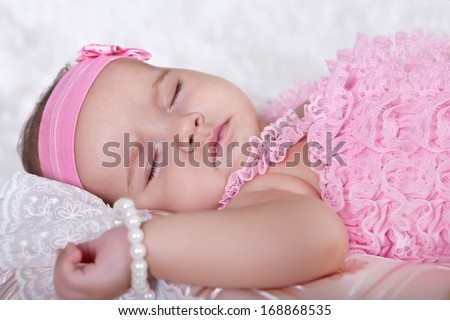Cute baby is sleeping, lying down on the back of a pink suit