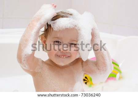 Cute baby is washing her hair in bath. The symbol of purity and hygiene education - stock photo