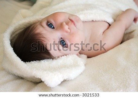 cute baby laying on fluffy towel - stock photo