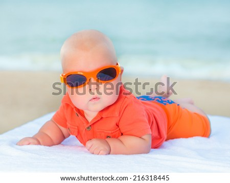 Cute baby laying on the sunbed at the beach - stock photo