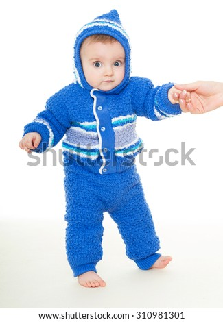Cute baby learning to walk. Beautiful happy baby in a blue dress . One, isolated on white.