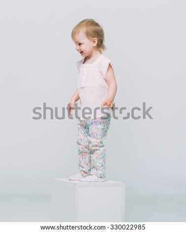 Cute baby little girl blonde studio portrait stand happy smiling  - stock photo