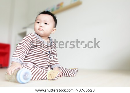 Cute Baby look left and take his feeding bottle with home background, child is a cute asian boy baby - stock photo