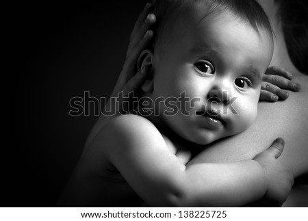 cute baby looking at hands of the mother in an embrace, monochrome - stock photo
