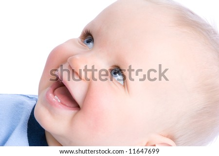 Cute baby looking diagonally and laughing, showing two teeth.  Shallow DOF, focus on the right eye. - stock photo