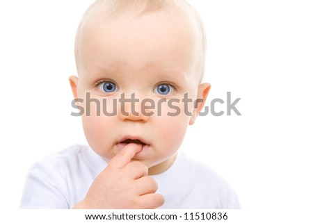 Cute baby looking into camera with a finger in his mouth, contemplating his next mischief. - stock photo