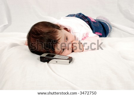 cute baby lying down by cellphone - stock photo