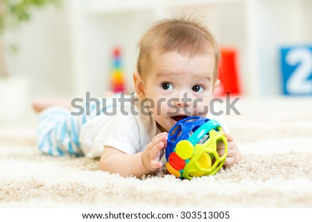 cute baby lying on soft carpet in children room - stock photo