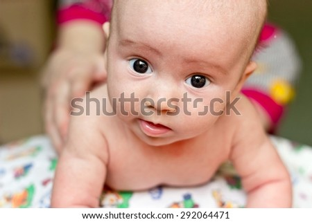 Cute baby lying on the fitness ball and looking at camera - stock photo